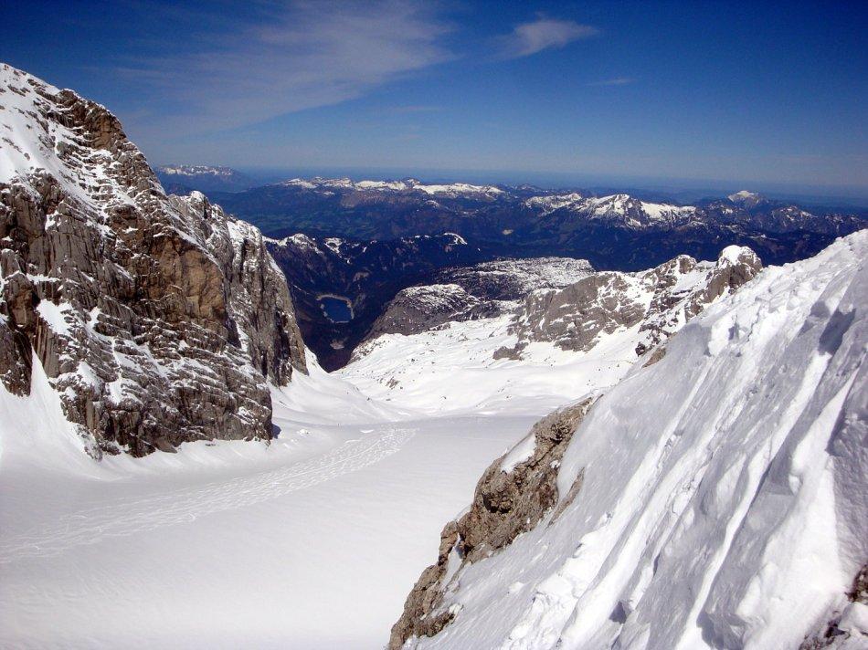 Auch unser Ausgangspunkt der vordere Gosausee ist im Tal erkennbar. Am Horizont sieht man bis in den Flachgau – links hinten der Untersberg, rechts hinten der Schafberg, beide noch mit Schnee bedeckt.