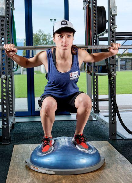 Tina Unterberger mach Langhantel Kniebeugen am Bosu Balance Trainer